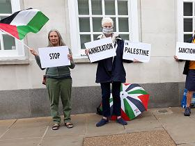 Two and a half protestors (I has to trim the photo for the home page) with a Palestinian flag and placards reading 'Stop annexation in Palestine, Sanctions'