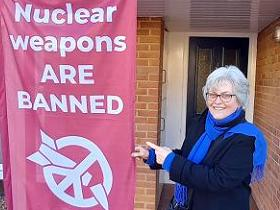 Banner: Nuclear weapons are banned, #nuclearban. Hilary in a scarf outside the front door of her house